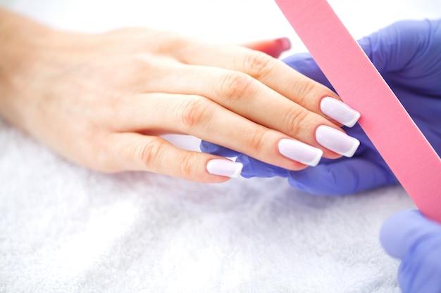 Manicure spa. manicure francesa no salão spa. mãos da mulher em um salão de beleza recebendo um procedimento de manicure. procedimento de manicure.