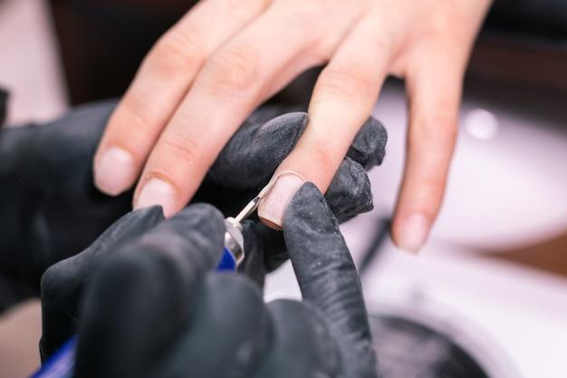 Manicure usa broca de lima de unha elétrica em salão de beleza