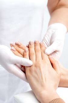 Manicure usando luvas fazendo massagem de cera nas mãos femininas com manicure em salão de beleza