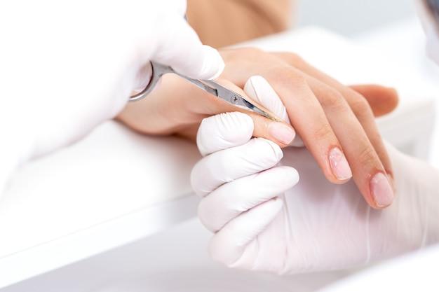 Manicure usando tesouras de manicure para remover cutículas de unhas femininas em salão de manicure