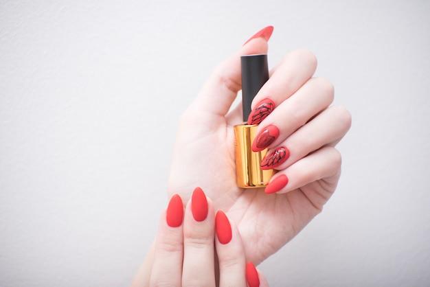 Manicure vermelho com um padrão. frasco com esmalte
