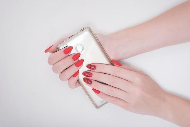 Manicure vermelho com um padrão. telefone inteligente na mão feminina. branco
