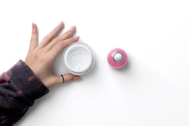 Manicured as mãos da mulher com capuz rosa na moda segurando creme cosmético