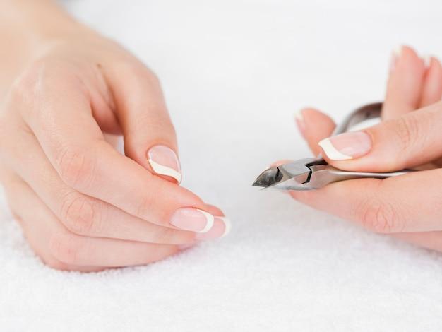 Manicured mãos segurando o cortador de unhas