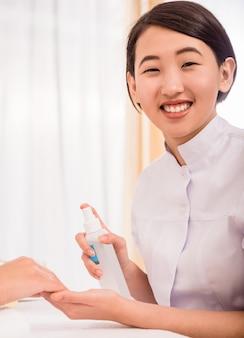 Manicuro asiático de sorriso que trabalha em pregos do seu cliente.