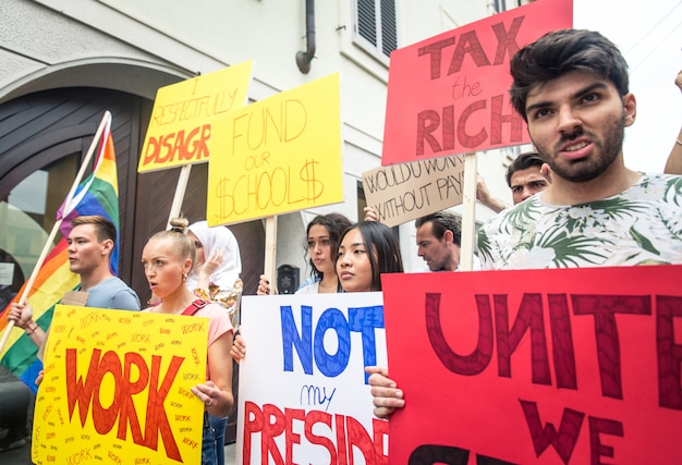 Manifestação pública na rua contra problemas sociais e direitos humanos. grupo de pessoas multiétnicas fazendo protesto público