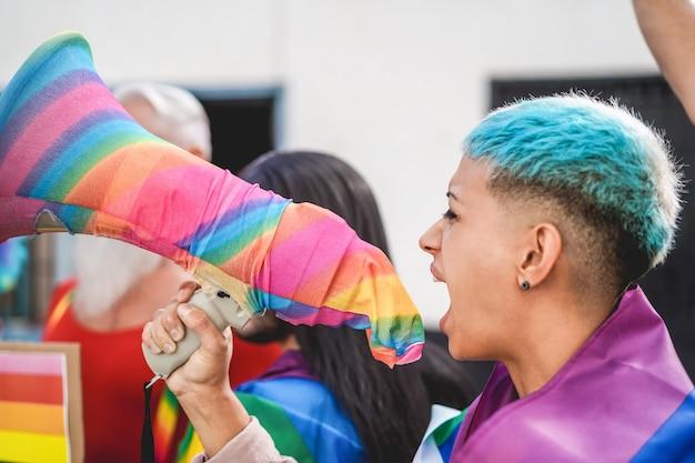 Manifestante lésbica gritando em protesto de orgulho lgbt pelos direitos de igualdade - foco principal no megafone