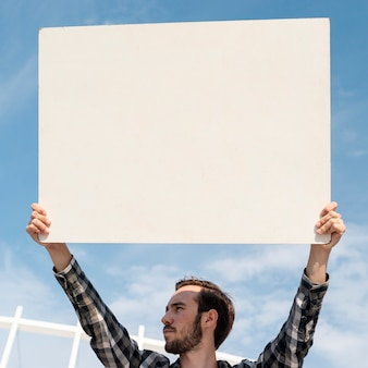 Manifestante segurando placa com mock-up para demonstração