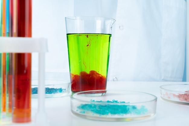 Manipulações com recipientes químicos de vidro de laboratório na mesa