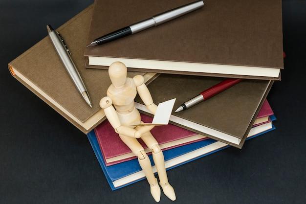 Maniqui leitura sentado em uma montanha de livros e canetas