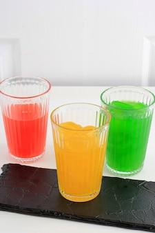 Manisan kolang-kaling de três cores (fruta em conserva da palmeira de açúcar). servido em vidro com fundo branco. esta sobremesa é um refresco típico da indonésia e durante o ramadã e idul fitri ou hari raya