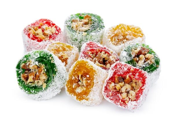 Manjar turco colorido com nozes em açúcar de confeiteiro isolado no branco