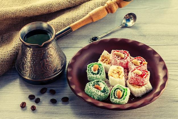Manjar turco em prato de barro com cezve de cobre com grãos de café na placa de madeira