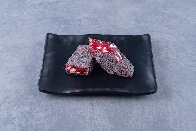 Manjar turco rahat lokum com pistache na placa preta.