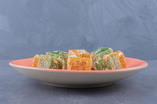 Manjar turco rahat lokumon prato laranja sobre fundo cinza.