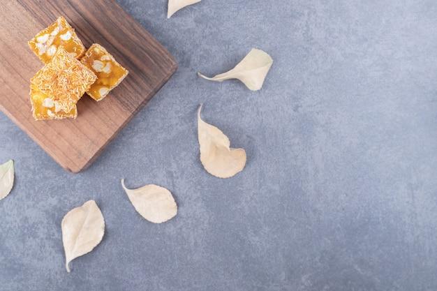 Manjar turco tradicional amarelo com amendoim na placa de madeira sobre fundo cinza.