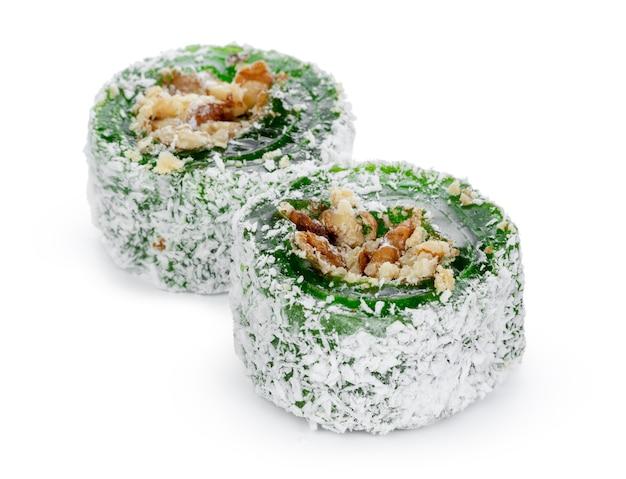 Manjar turco verde com nozes em açúcar de confeiteiro isolado no branco