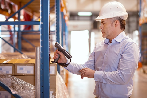 Manjedoura séria e inteligente segurando um scanner enquanto verifica o equipamento do armazém
