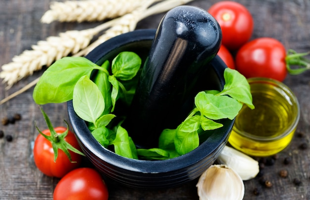 Manjericão em uma tigela, tomate e óleo