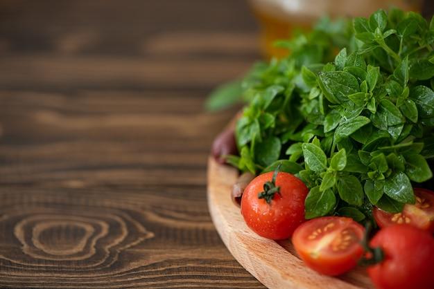 Manjericão fresco com tomates e azeitonas em uma placa de madeira