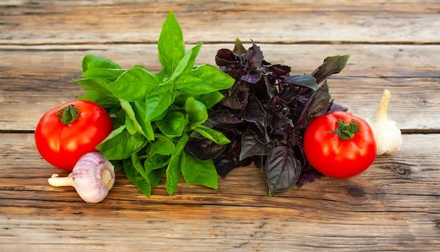 Manjericão verde e roxo fresco, tomate vermelho e alho em uma mesa rústica de madeira