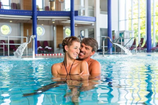 Mann e mulher na piscina do spa termal de bem-estar