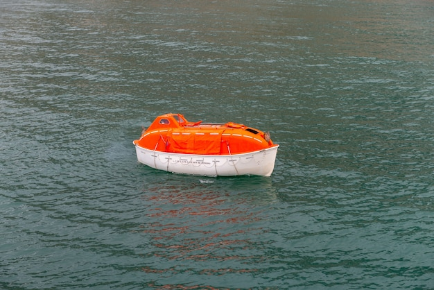 Manobrando o barco salva-vidas alaranjado na água em águas árticas, svalbard. abandone a broca do navio. treinamento de barco salva-vidas. homem a bordo de broca.