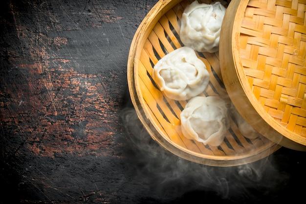 Manta de bolinhos quentes em um vaporizador de bambu na mesa rústica escura.