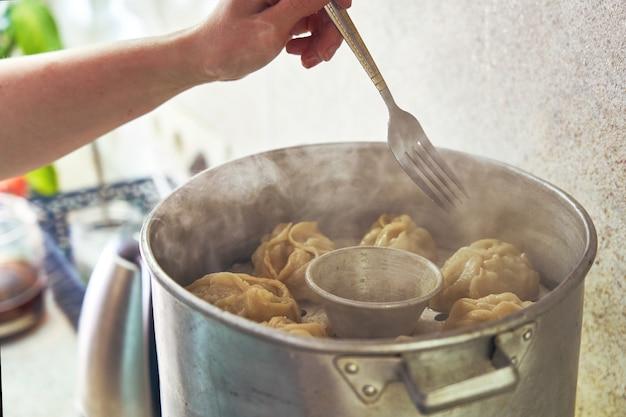 Manta de comida nacional uzbeque, como bolinhos de massa, em um vapor, comida no vapor.