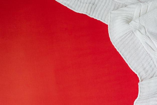 Manta de malha branca sobre um fundo vermelho no canto. postura plana. copiar espaço