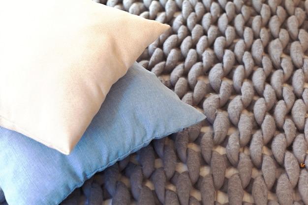 Manta de malha cinza com travesseiros