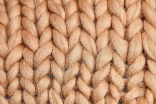 Manta de malha merino lã artesanal grande, fio super robusto, conceito moderno. close-up de cobertor de malha, fundo de lã de merino. manta de designer feita de lã esfumaçada bege