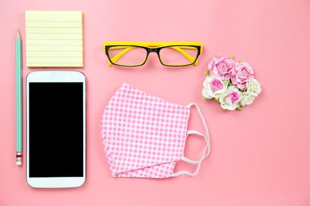 Manta de máscara cirúrgica rosa e óculos amarelos com tela de traçado de recorte móvel de lápis no backgroud rosa estilo pastel flatlay topview copyspace