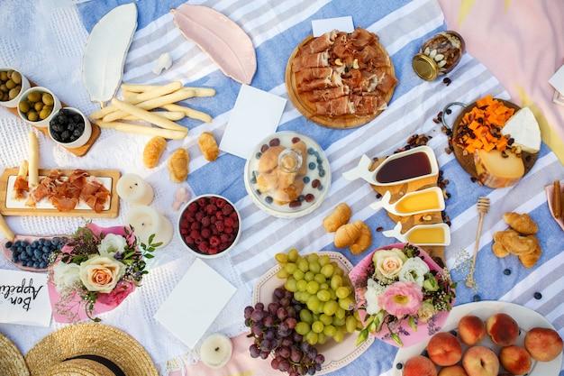 Manta de piquenique de verão com comida saborosa e lanches nele. fins de semana de verão