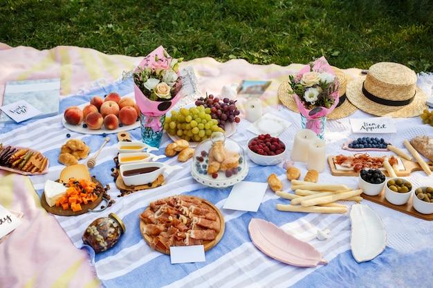 Manta de piquenique de verão com comida saborosa e lanches nele