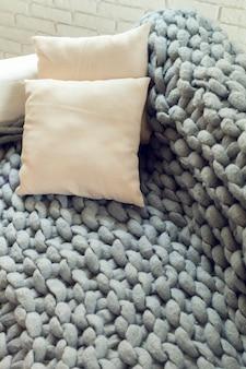 Manta gigante de malha cinza com almofadas