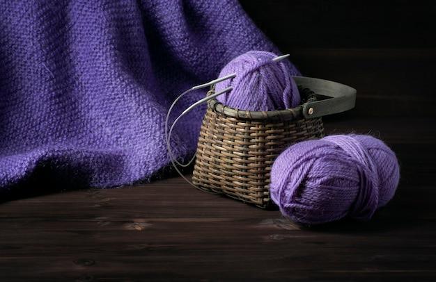 Manta roxa de malha e uma cesta de vime com fios roxos sobre um fundo escuro de madeira.