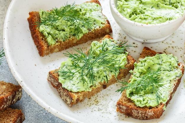 Manteiga com endro verdes no pão de centeio com sementes de girassol
