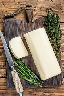 Manteiga cortada em fatias de bloco em uma placa de madeira com ervas