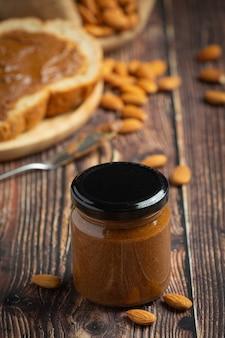 Manteiga de amêndoa orgânica crua em fundo de madeira escura