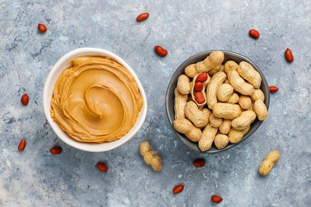 Manteiga de amendoim caseira com amendoins na mesa de concreto cinza, vista superior