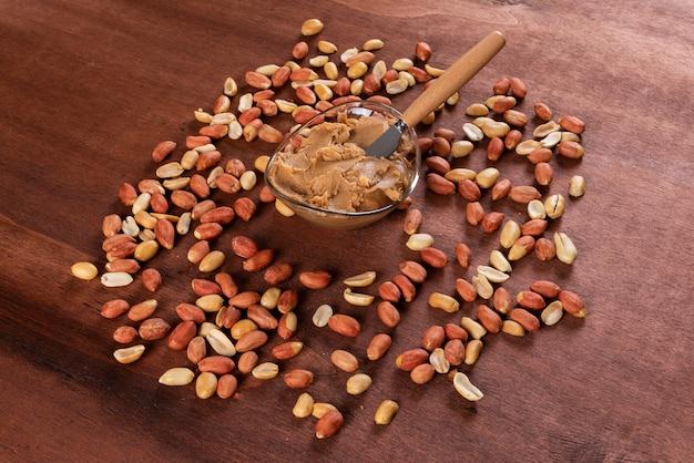 Manteiga de amendoim, cercada por amendoins na horizontal de madeira