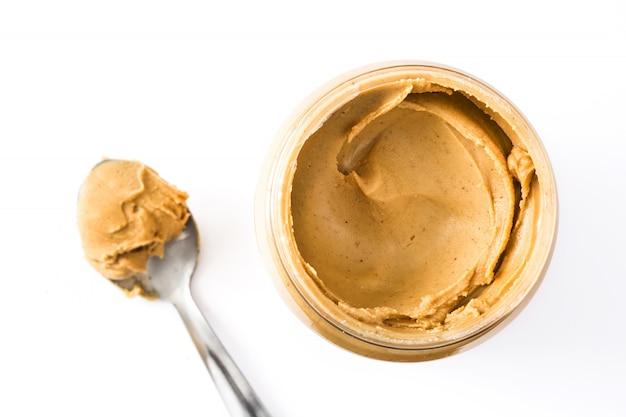 Manteiga de amendoim cremosa e colher isoladas na vista superior de superfície branca
