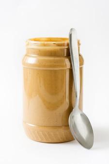 Manteiga de amendoim cremosa e colher isolado na superfície branca