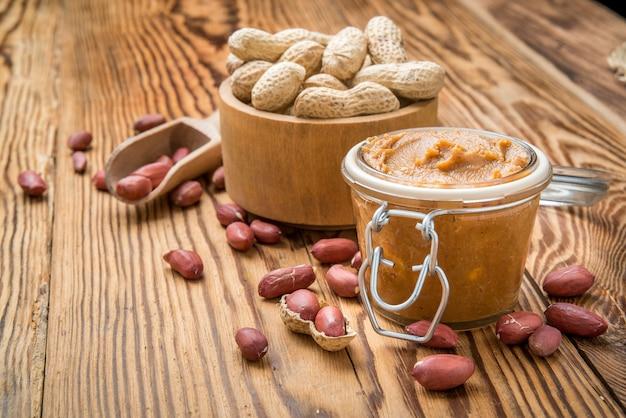 Manteiga de amendoim cremosa na mesa de madeira.
