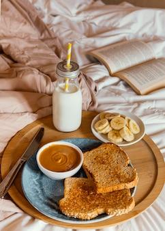 Manteiga de amendoim de alto ângulo, leite e pão