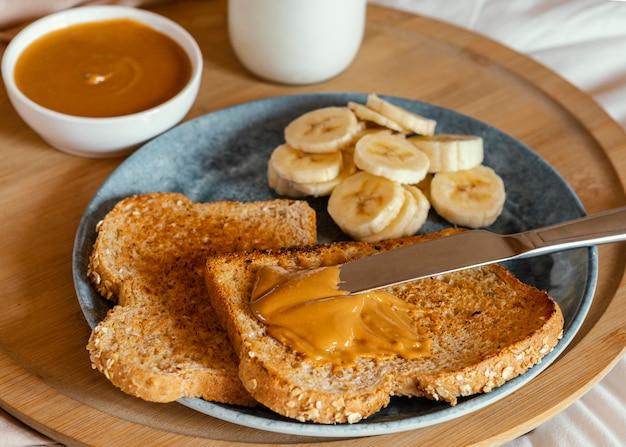 Manteiga de amendoim de alto ângulo na fatia de pão