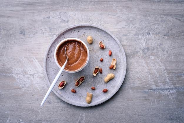 Manteiga de amendoim e amendoins em fundo cinza, vista superior