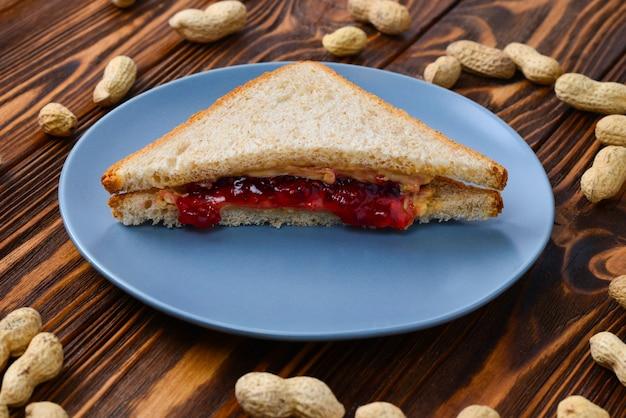 Manteiga de amendoim e sanduíche de geleia na mesa de madeira.