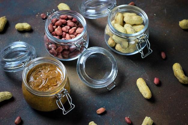 Manteiga de amendoim em jar e amendoins em frascos